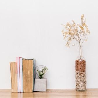 Composição de plantas secas e livros sobre a mesa