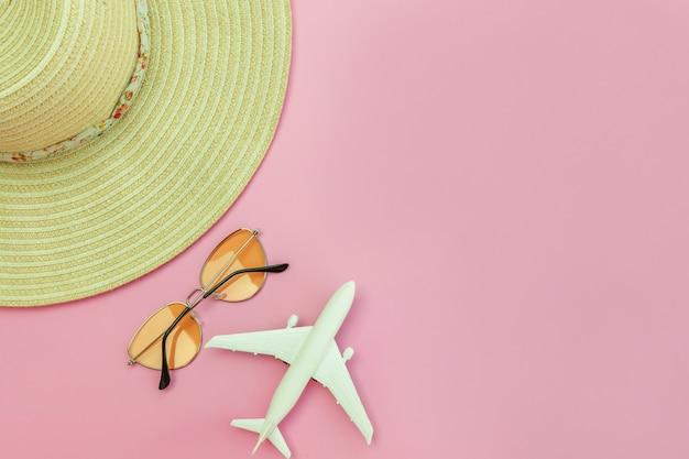 Composição de praia verão. mínimo plano simples leigos com óculos de sol avião e chapéu isolado em rosa pastel. conceito de viagem de aventura de viagens de férias. vista superior cópia espaço.