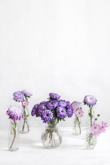Composição de primavera com flores de crisântemo em vasos de vidro em um fundo branco turva, copie o espaço.