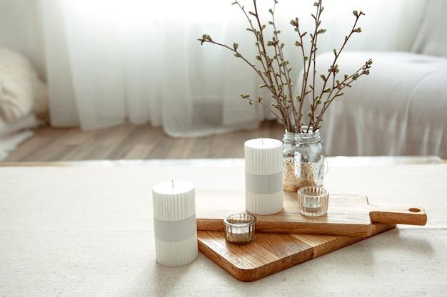 Composição de primavera com galhos jovens em um vaso com velas no interior da sala.