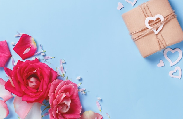 Composição de primavera com rosas, pétalas, corações e caixa de presente em um fundo pastel