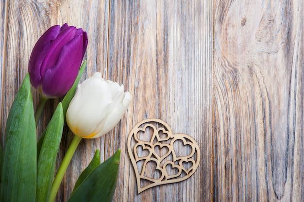 Composição de primavera com tulipas e coração de madeira