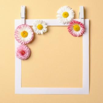 Composição de primavera feita com flores coloridas e borda de quadro de papel sobre fundo amarelo pastel.