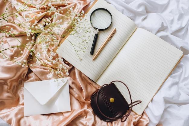 Composição de primavera, flores de gipsófila brancas com caderno e lupa no tecido de cetim dourado