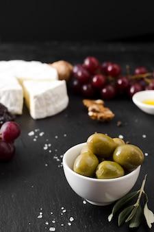 Composição de queijo e azeitonas de alto ângulo em fundo preto