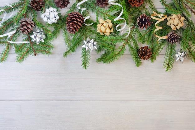 Composição de ramos de abeto, fitas de ouro e prata e cones sobre um fundo claro de madeira.