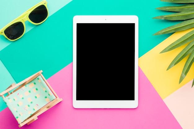 Composição de relaxamento de praia com tablet na superfície multicolorida