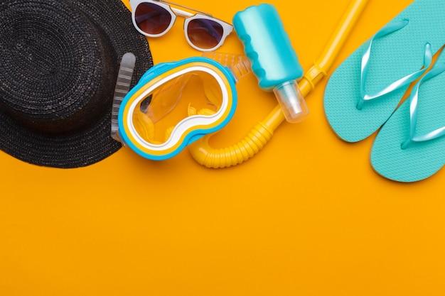 Composição de roupa de praia e acessórios em um fundo amarelo