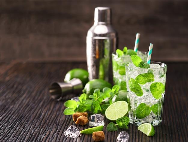 Composição de rum em copos para mojitos e coqueteleira sobre balcão de madeira.