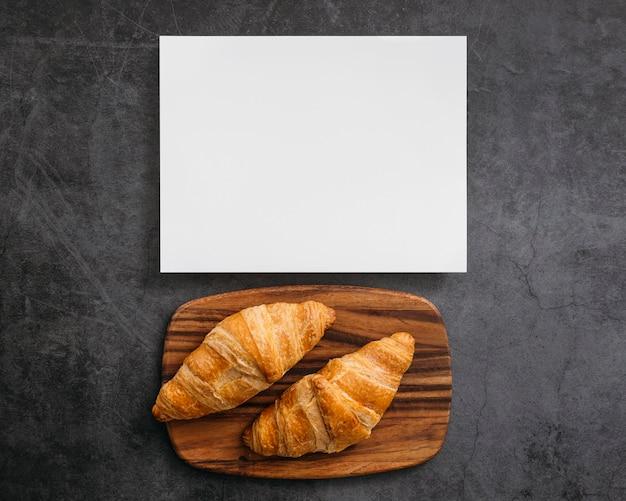 Composição de saborosos croissants de café da manhã com cartão vazio