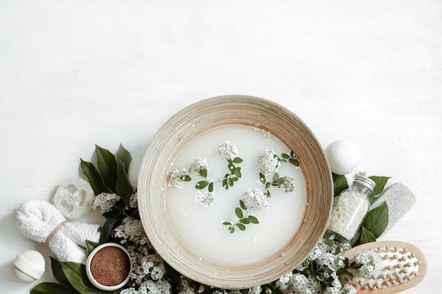 Composição de spa com água para tratamentos de beleza e flores frescas