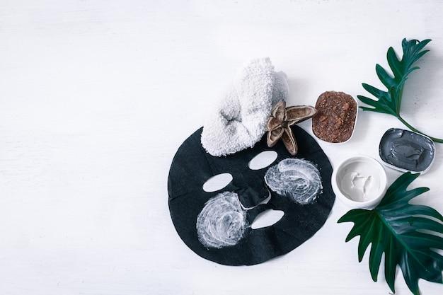 Composição de spa com artigos de cuidado facial com máscara preta e folhas.