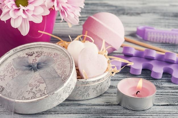 Composição de spa com bombas de banho-de-rosa, margarida flores, vela acesa
