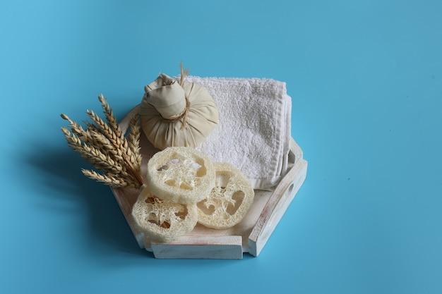 Composição de spa com bucha bolsa de ervas e trigo em um fundo azul