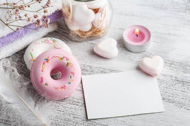 Composição de spa com donuts de bomba de banho e nota vazia sobre fundo rústico em estilo monocromático.