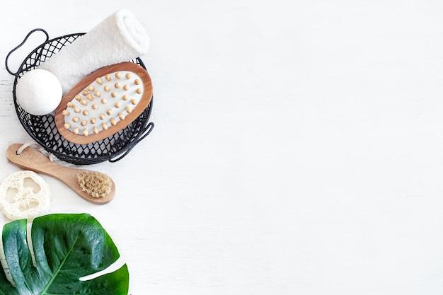 Composição de spa com escova de massagem e outros acessórios de banho na cesta em fundo branco com folha de monstera.