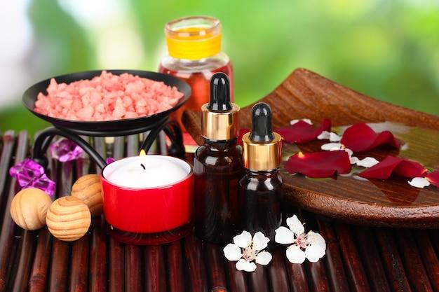 Composição de spa com óleos aromáticos na mesa em fundo brilhante