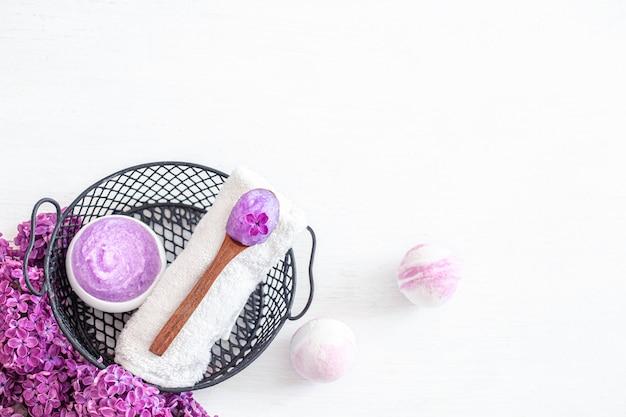 Composição de spa com produto cosmético lilás, bombas de banho e flores lilás. cuidados com a pele e cuidados com o corpo