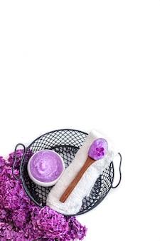 Composição de spa com produto cosmético lilás e flores lilás. conceito de cuidados com a pele e cuidados com o corpo.