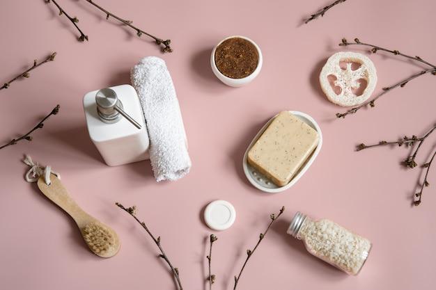 Composição de spa com sabonete, escova, bucha, sal marinho e toalha entre galhos de árvores de primavera.