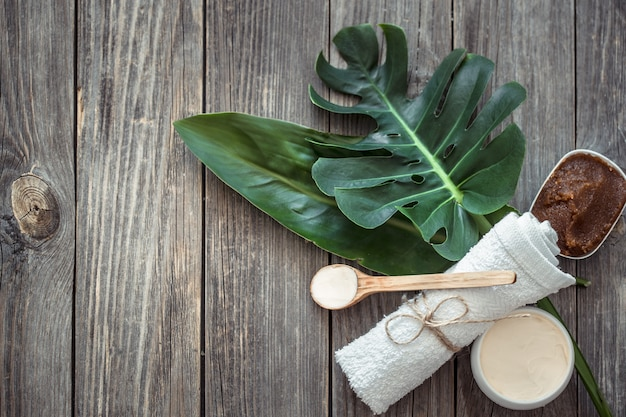 Composição de spa com toalhas e folha tropical em uma parede de madeira.
