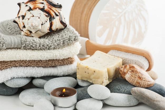 Composição de spa com toalhas, velas acesas, sabão