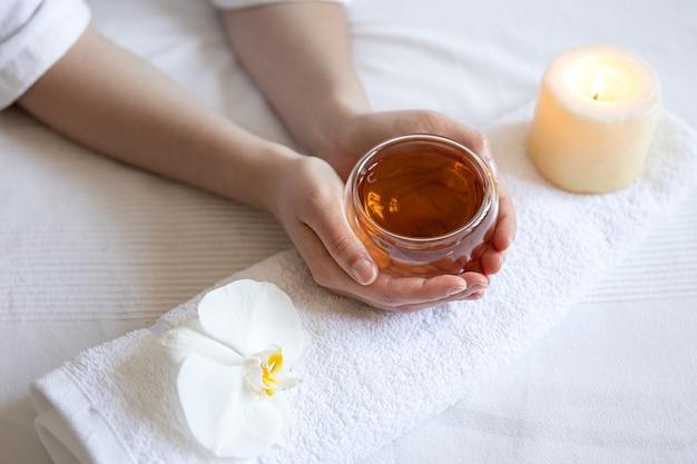 Composição de spa com uma xícara de chá em mãos femininas, uma orquídea e uma vela
