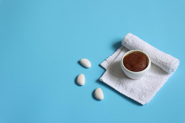 Composição de spa minimalista com esfoliante natural e toalha sobre fundo azul, espaço de cópia, conceito de cuidados com a pele do rosto e corpo.