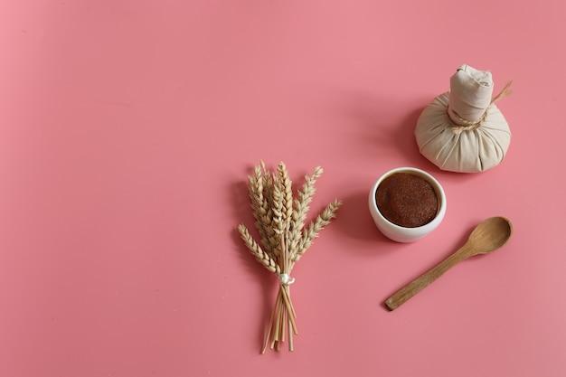 Composição de spa minimalista com esfoliante natural, saco de massagem de ervas, colher de pau e trigo em um fundo rosa, copie o espaço.