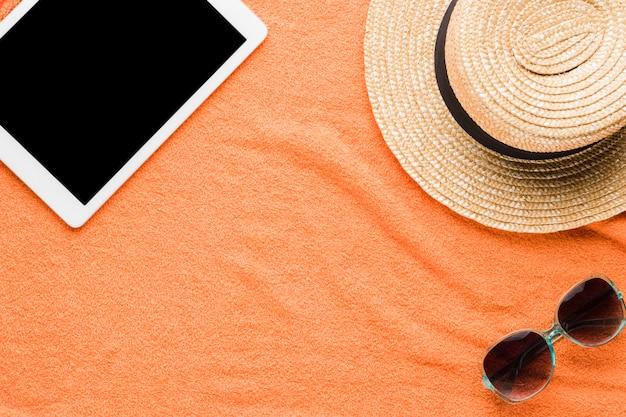 Composição de tablet óculos escuros e chapéu