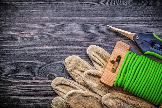 Composição de tesouras de jardim amarram luvas de segurança de arame no conceito de jardinagem de tábuas de madeira vintage