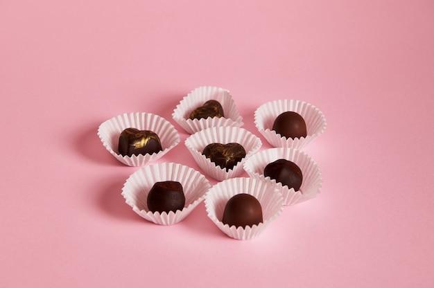 Composição de trufas de chocolate e bombons em embalagens de papel na superfície rosa com espaço de cópia. conceito de dia do chocolate