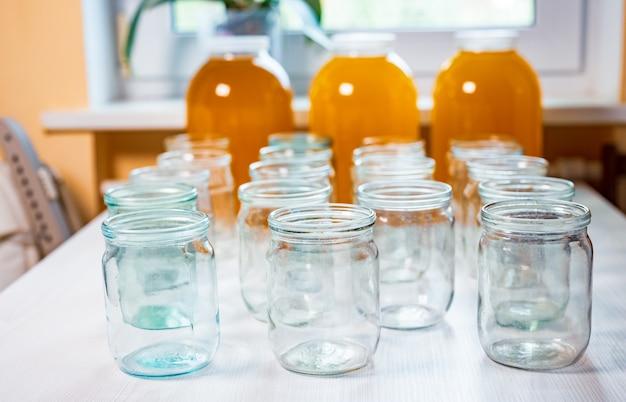 Composição de um grande número de potes de vidro transparente vazio e três grandes potes de vidro transparente com mel amarelo doce, em pé sobre uma grande mesa branca contra um fundo de luz solar intensa