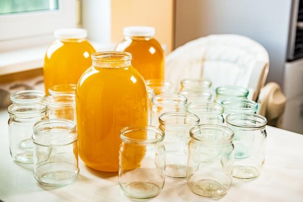 Composição de um grande número de potes de vidro transparentes vazios e três grandes potes de vidro transparente com mel amarelo doce, em pé sobre uma grande mesa branca contra um fundo de luz solar intensa