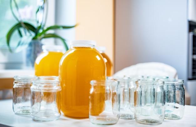 Composição de um grande número de potes e três potes de mel sobre uma mesa branca contra um fundo de luz Foto Premium