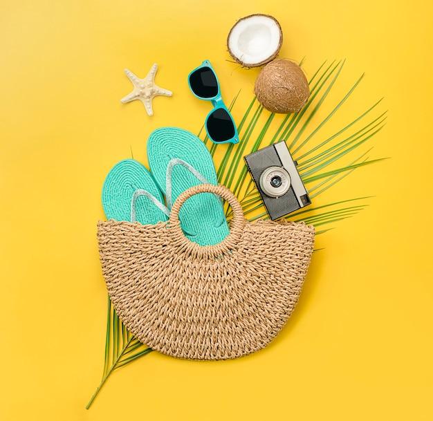 Composição de uma bolsa de praia, chinelo, câmera, folha de palmeira, óculos de sol, coco e estrela do mar