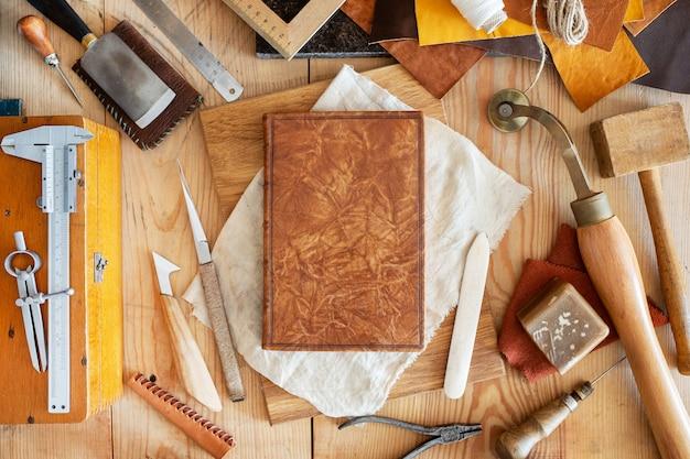 Composição de várias ferramentas comerciais para o artesanato de encadernação e estampagem manual