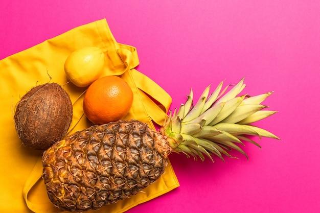 Composição de várias frutas exóticas frescas com um saco de algodão amarelo sobre um fundo amarelo. lay plana. conceito de comida.