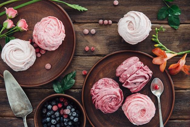 Composição de vários merengues de mirtilo, cerejas e flores na superfície de madeira escura
