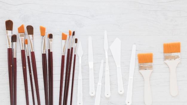 Composição de vários pincéis e facas de paletes