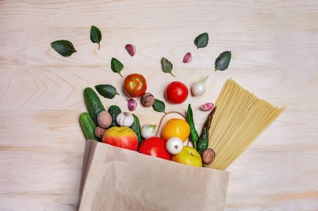 Composição de vegetais, frutas, alho, cebola, nozes e espaguete em um saco de papel
