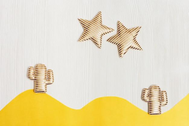 Composição de verão com brinquedo macio, dois cactos dourados e estrelas brilhantes no deserto em madeira branca