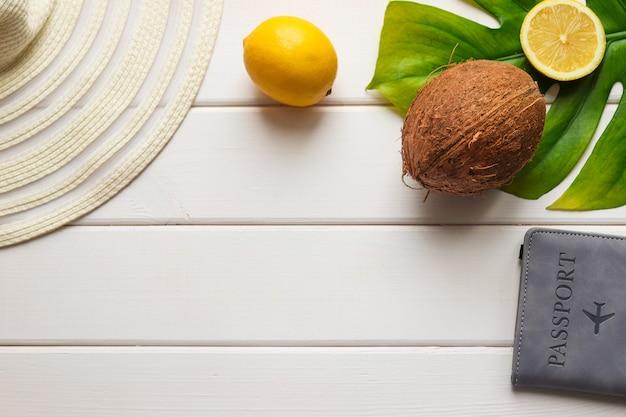 Composição de verão com coco, limão, chapéu de folha monstera e passaporte em uma mesa de madeira branca