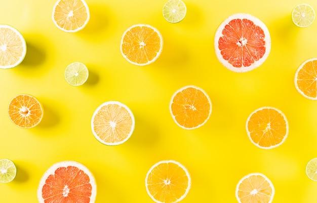 Composição de verão feita de laranja, limão ou lima em papel amarelo pastel