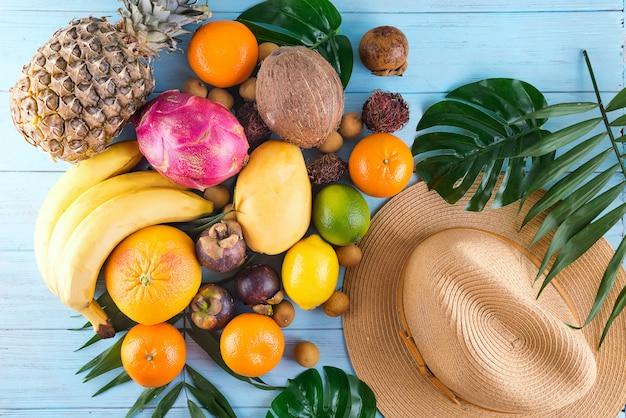 Composição de verão. folhas de palmeira tropical, chapéu, muitas frutas no fundo de madeira azul.