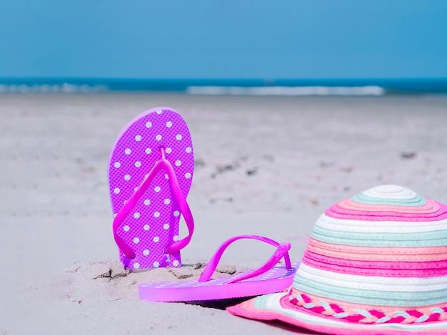 Composição de verão luz solar. chinelos de praia na areia do oceano tropical. contra o mar azul e a parede do céu. acessórios de praia conceito de férias de verão de férias na praia, passeio no mar, verão ensolarado quente
