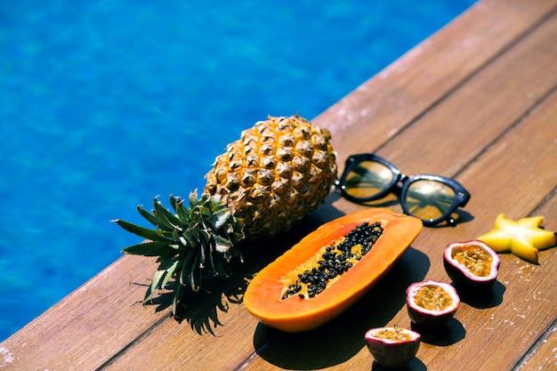 Composição de verão perto da piscina e piso de madeira, sunglasse elegante hipster.