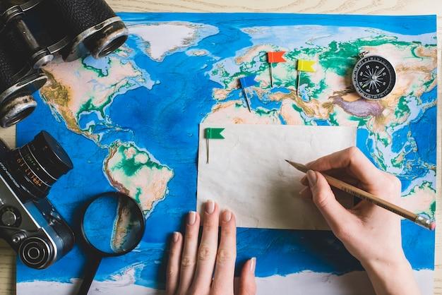 Composição de viagem com mão segurando um lápis