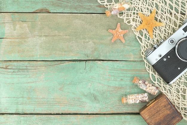 Composição de viagens com estrelas do mar, conchas, câmera fotográfica e redes marítimas