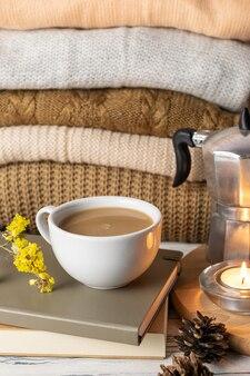 Composição de vida ainda estilo de vida hygge com café, velas, livros e mantas de malha ou blusas